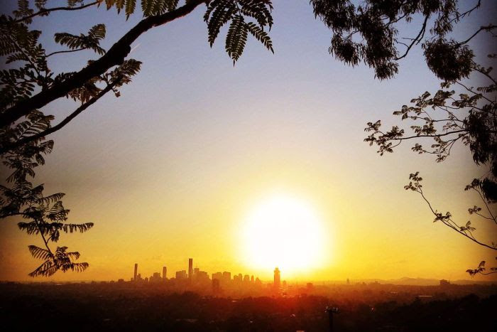 Sun sets at Mt Coot-tha with trees in silhoulette, with Brisbane city buildings in the distance.