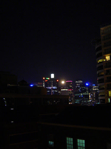 moon rising between the buildings