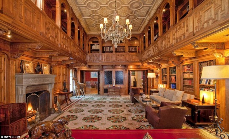 New chapter: The two-story library comes with an open fireplace, wood paneling and carved ceiling