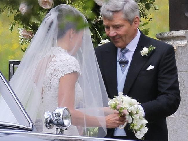 Michael Middleton helps his daughter out of the vintage car before entering the church. Picture: Flynetpictures.co.uk/IMP Features