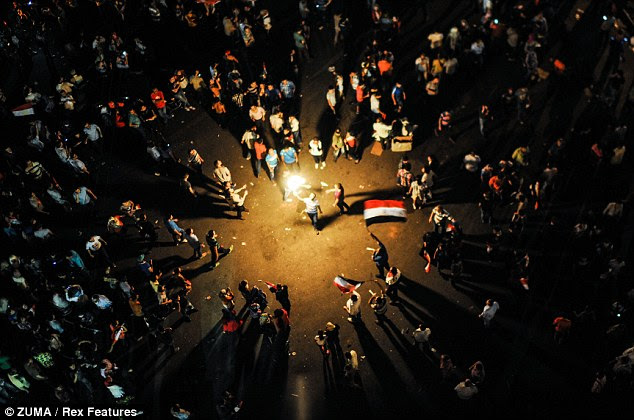 Lighting the way ahead: Protesters out in force in Cairo's Tahrir Square as the country's armed forces move in to depose Morsi following days of unrest