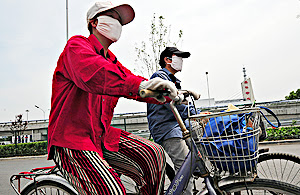 [Cyclists wear masks while riding in Beijing last week. Beijing authorities have insisted air quality in the Chinese capital has improved enough to meet its Olympic targets.]