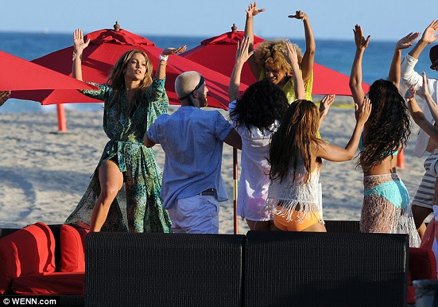 Group dance off: The singer was joined by a slew of stunning bikini clad dancers on the beach