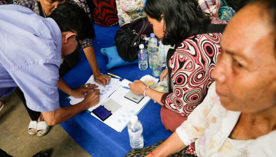 CNRP supporters sign and thumbprint a petition addressed to the National Assembly yesterday at the party's headquarters in Phnom Penh.