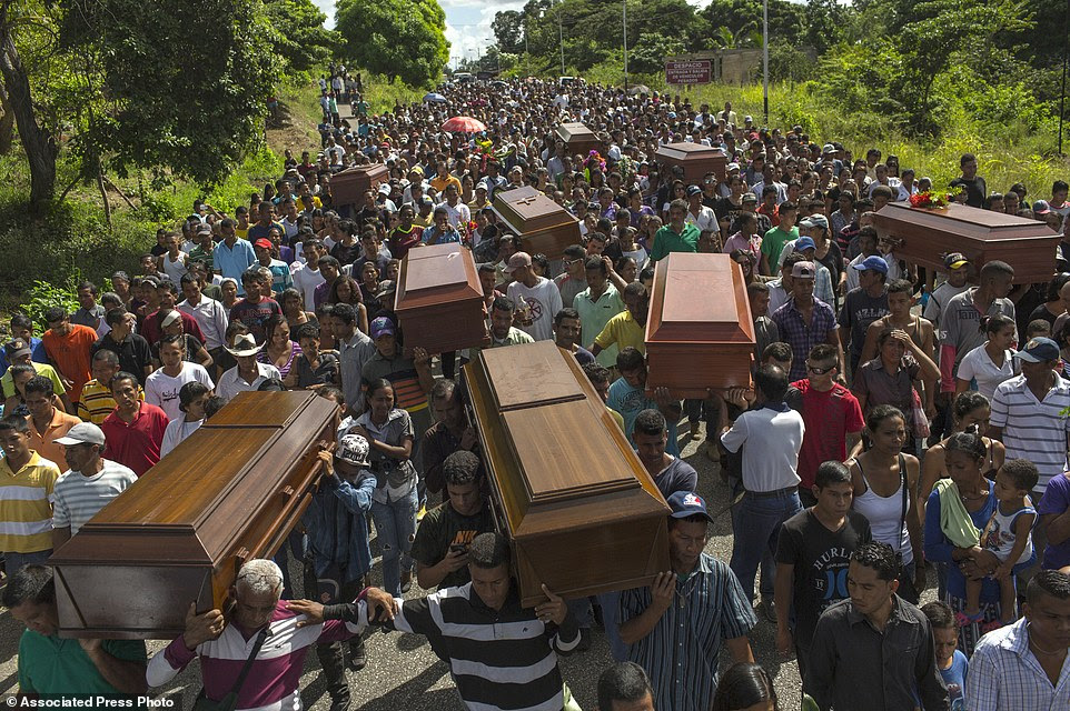 Villagers carry the remains of nine slain men from a fishing family to the cemetery in Cariaco, Sucre state, Venezuela. Five law enforcement officers were charged with storming the village and killing these men, who were widely thought to have belonged to a gang