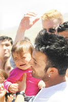 Tarkan holding a child during his visit to southwestern Turkey