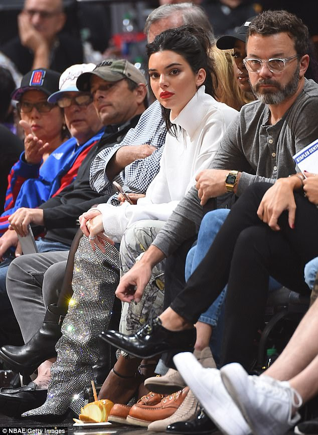 The game: Kendall wore a casual ensemble with a turtleneck sweatshirt and a pair of ripped jeans