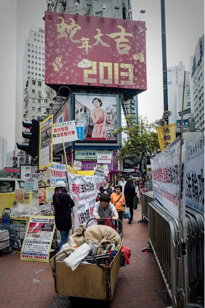 A woman pushes a loaded cart past a billboard set up for the Chinese New Year, in Hong Kong, on February 5, 2013
