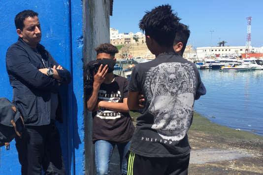Khalid Ait-Boughouliden,éducateur spécialisé, avec des enfants candidats à l'émigration sur le port de Tanger, le 3 mai.