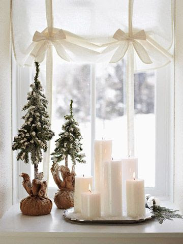 Use Window Space  Simplicity is key for small-space decorating. White pillar candles, placed on a silver tray, add elegance to a windowsill. Two faux dwarf evergreens, wrapped in burlap, add a bit of color to the wintry scene.