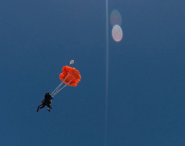 My videographer continues to film me and my tandem instructor as she falls away from us after our parachute deploys above the ground at Oceanside, California...on October 4, 2018.