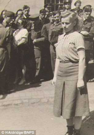 A woman is marched before gathered crowds