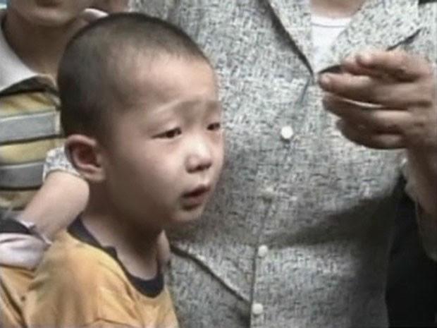 Menino é visto com seus familiares após ser resgatado de uma fenda entre paredes na China (Foto: CCTV/Reuters)