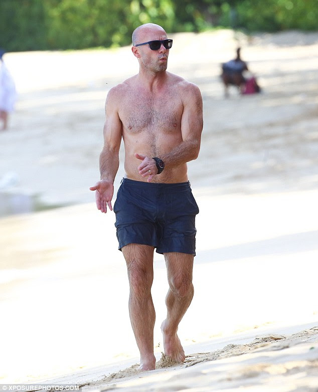 Off he pops: The sporting ace looked hunky during his stroll along the shore