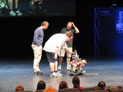 """Eemeli, Jukka and Topi wondering about the little doggy """"robot"""" on stage"""