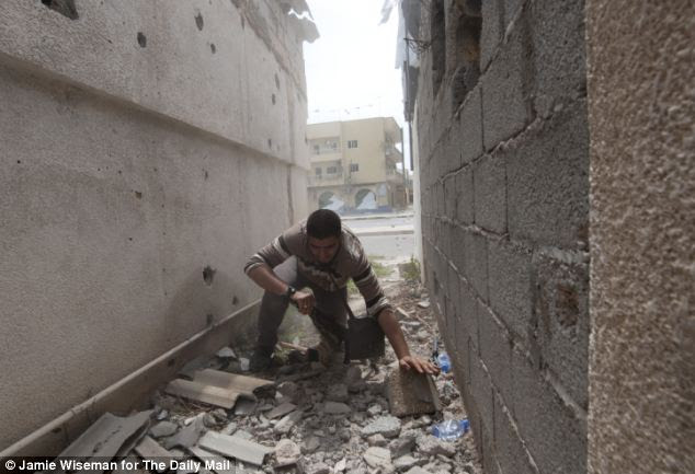 Scramble: Rebel fighter and temporary guide Abu Baker moments before he became the second person to be shot by the sniper