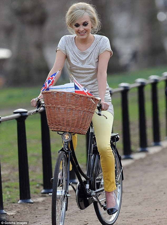 Riding high! Fearne also donned a pair of yellow skinny jeans as she rode a bike around London