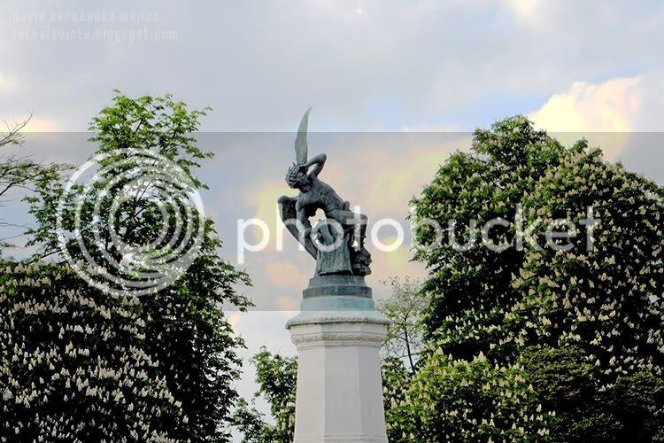 Escultura del Ángel caído, entre árboles con un cielo tenebrista, en el Parque del Buen Retiro, Madrid