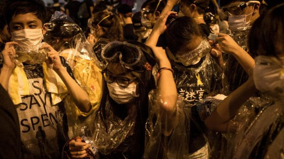 Protesters put on goggles and wrap themselves in clear wrap after hearing a rumour that police were coming with tear gas outside the Hong Kong Government Complex.