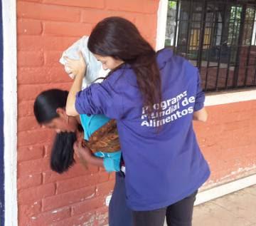 Patricia ayuda a una madre de la localidad de Cotacahi en Ecuador a cargar su canasta de alimentos.