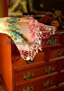 an embroidered linen handkerchief atop an old small chest