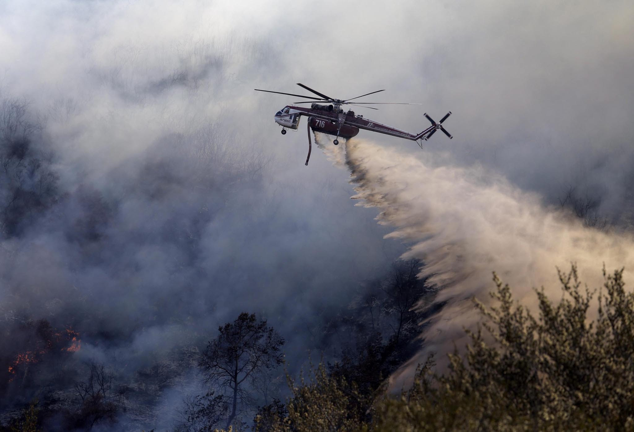 A chopper drops fire retardant on the Blue Cut fire, northeast of Los Angeles, California, USA