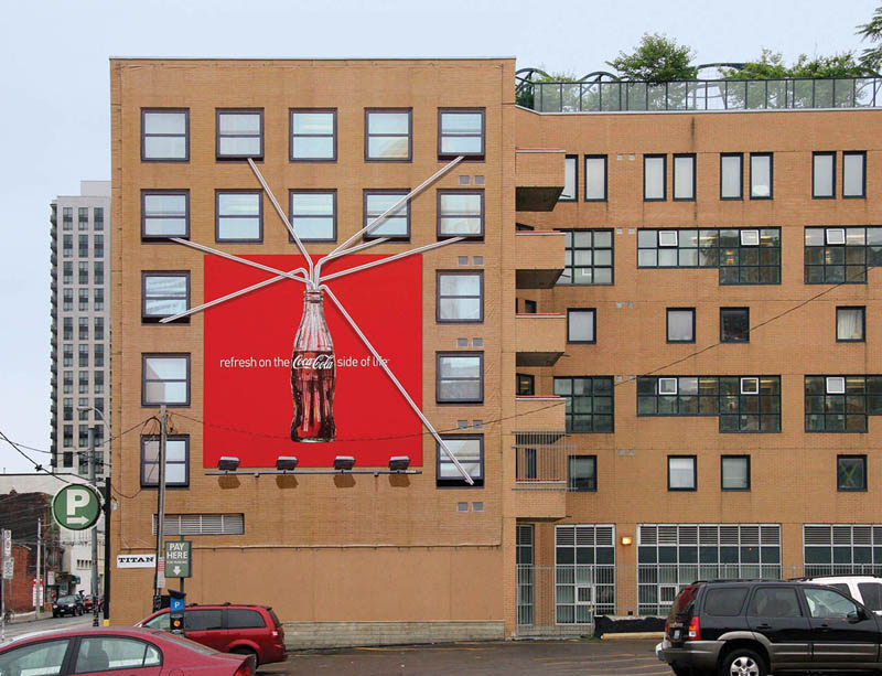coca cola billboard shows apartments with straws into large coke bottle