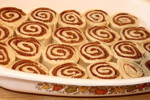 Uncooked cinnamon roll buns in pan.
