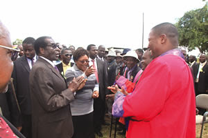 Zimbabwe President Mugabe greets Chief Negomo at the launch of First Choice Wholesale while Vice President Joice Mujuru looks on in Mt Darwin on April 20, 2012. by Pan-African News Wire File Photos