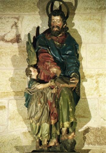 Escultura de madera policromada representando al apóstol San Mateo de pie, apoyándose para escribir su evangelio en la rodilla izquierda, que mantiene algo levantada. A su derecha un ángel le ofrece un tintero