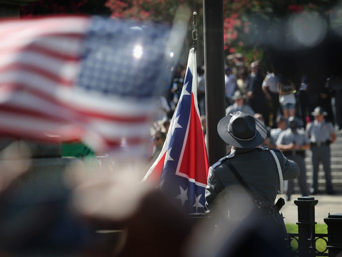 A South Carolina state police honor guard lowers the