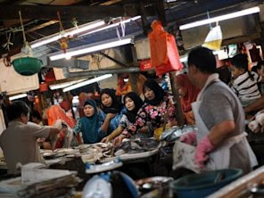 Customers buy fish from a stall …