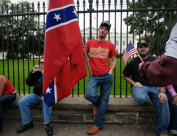 WASHINGTON, DC - OCTOBER 13: Michael Ashmore, of Hooks, Texas, leans against the White House fence with his confederate flag.  He and other demonstrators have walked here after attending a rally at the WWII Memorial to protest its' closing on October, 13, 2013 in Washington, DC. (Photo by Bill O'Leary/The Washington Post)