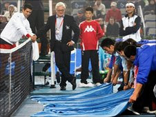 Novak Djokovic (left) and David Ferrer look on as the court is dried