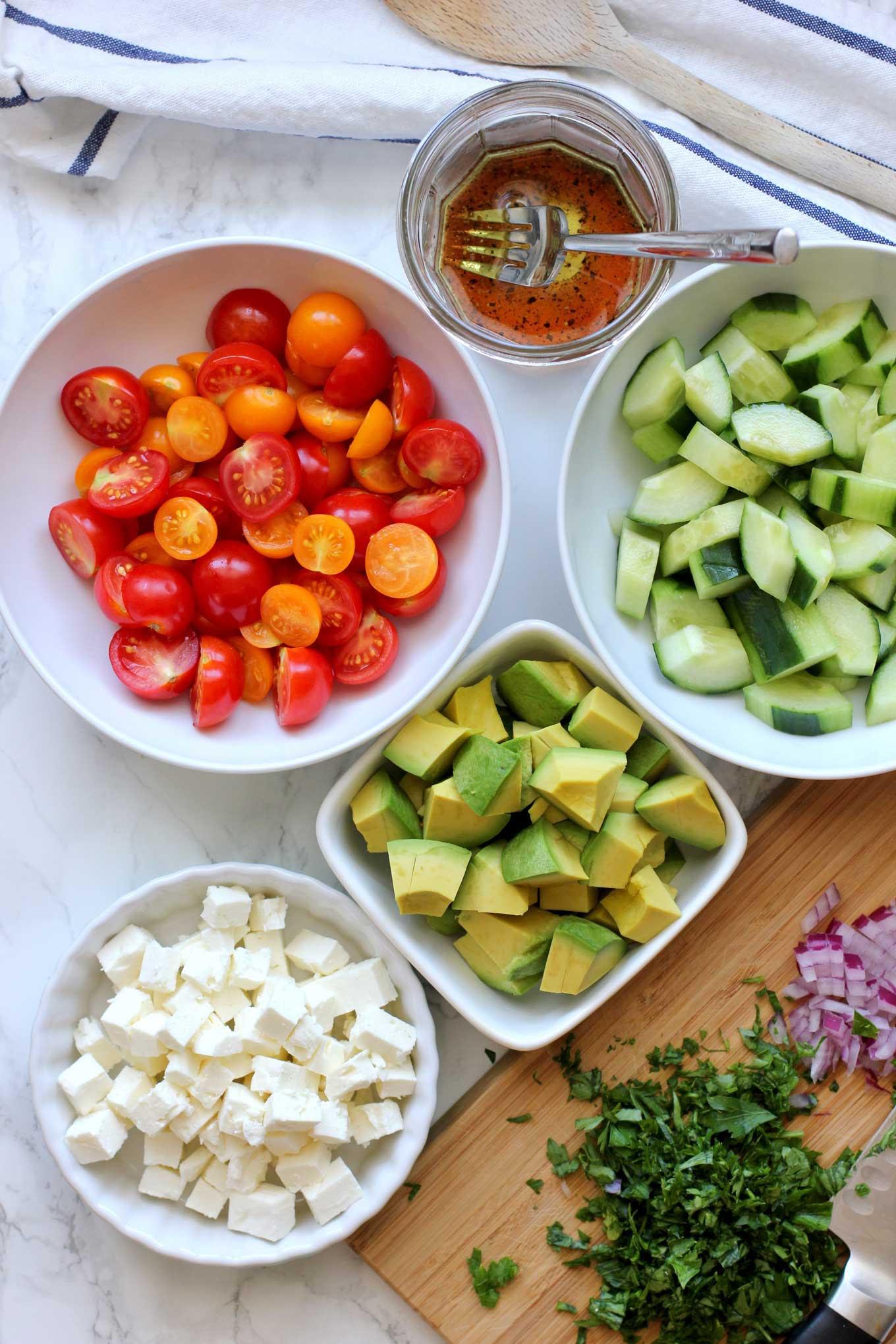 Ingrédients pour faire une salade de tomates, concombres et avocats sur un comptoir en marbre.