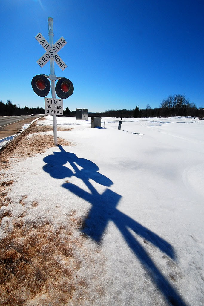 A railroad crossing sign, and its shadow.