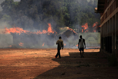 Youths walk towards burning houses in Bossangoa, north of Bangui January 2, 2014.  by Pan-African News Wire File Photos