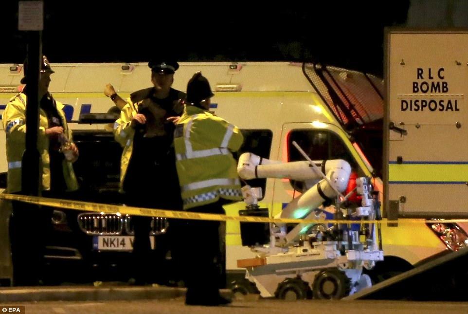 Os oficiais observam como um robô de destruição de bomba do Royal Logistics Corps se move no lugar atrás de um cordão de segurança fora de Manchester Arena