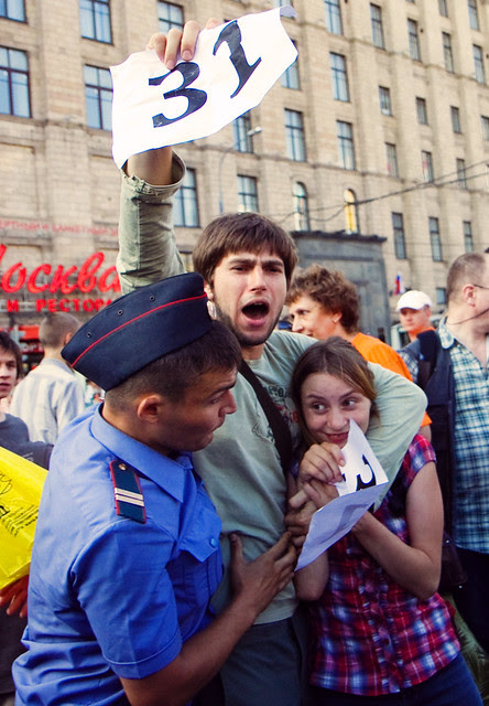 Russian policemen detain opposition party supporters during a protest rally in central Moscow