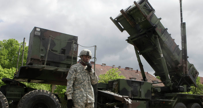 U.S. soldier stands next to a Patriot surface-to-air missile battery at an army base in Morag, Poland