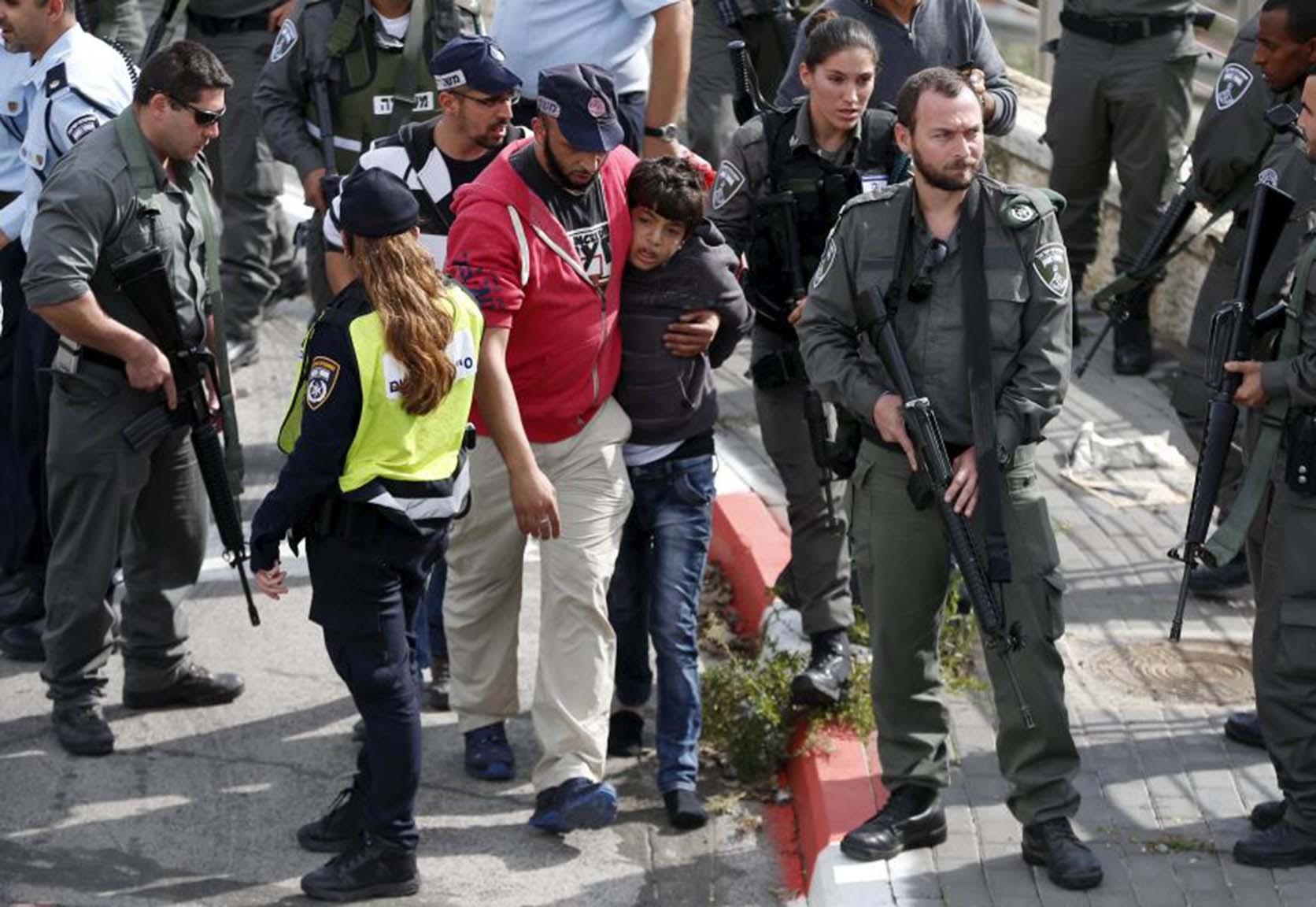Israeli police lead away a Palestinian minor in Pisgat Zeev
