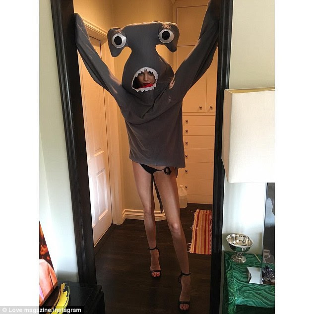 Leggy lady: The gorgeous star paraded her superbly smooth supermodel stems in the bottom-skimming hammerhead-shark costume beneath which she wore a black bikini