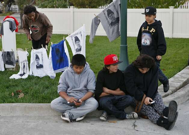 Tonia Coleman hangs clothing printed with Andy Lopez Cruz's image while Fernando Alducin (center), Cristian Sev, Marisol Hernandez and Carlos Sev wait outside Andy's viewing service in Windsor. Photo: Raphael Kluzniok, The Chronicle