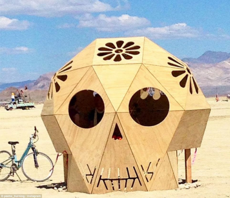 Hiding out: Some partygoers hang out inside a large skull in the desert - of course
