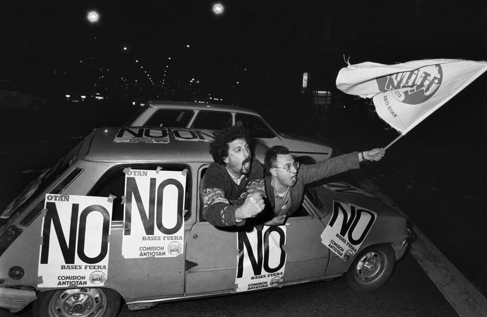 """Manifestación anti-OTAN celebrada en Madrid el 10 de marzo de 1986, el mismo día en que se cerró la campaña del referéndum para la incorporación de España a la alianza. Dos jóvenes gritan asomados a la ventanilla de un coche con carteles de """"OTAN no, bases fuera""""."""