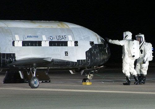 Two technicians wearing hazmat suits conduct a post-landing checkout on the OTV after its return home from space on December 3, 2010.