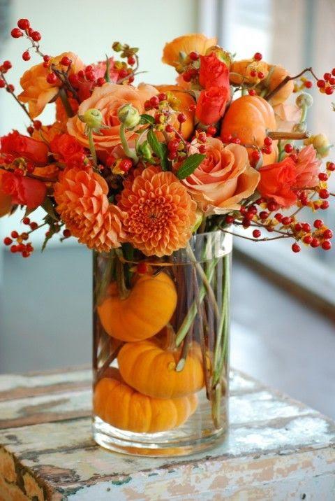 eine kühne floral arrangement in burnt orange und Kürbisse in der vase für eine Herbst-Hochzeit