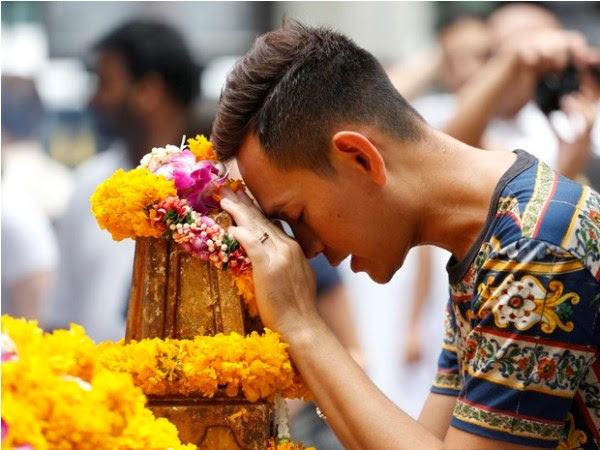 Homem faz oração nesta segunda-feira (24) no santuário de Erawan, na Tailândia, uma semana após atendado terrorista que matou 20 pessoas (Foto: AP Photo/Sakchai Lalit)