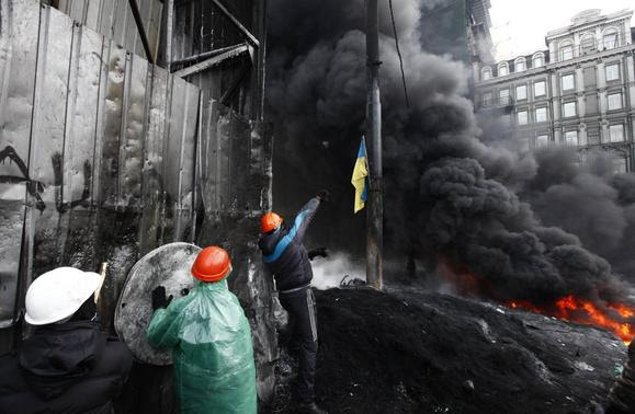 An anti-government protester (R) throws a stone at a barricade, at the site of clashes with riot police in Kiev January 25, 2014. Ukrainian President Viktor Yanukovich, in what appeared to be an offer of concessions to the opposition amid violent protests against his rule, pledged on Friday to reshuffle the government next week and to amend sweeping anti-protest laws. REUTERS-Vasily Fedosenko