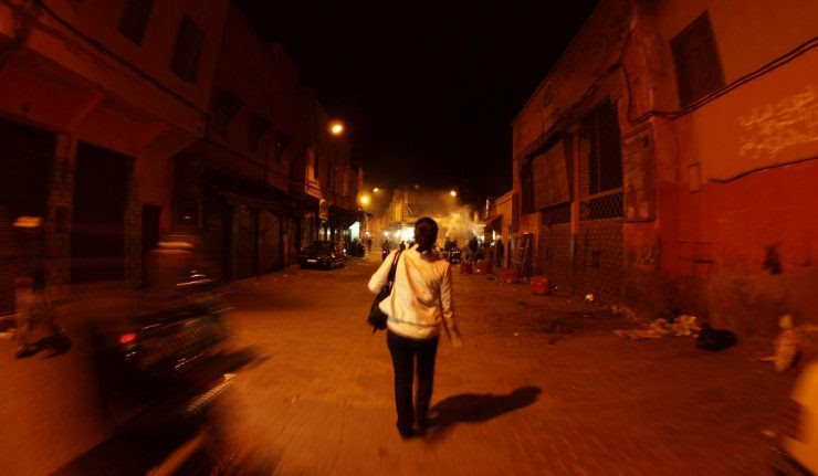 An woman walks late at night in the medina of Marrakech, Morocco (@torrenegra).